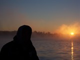 man on boat watching sunrise
